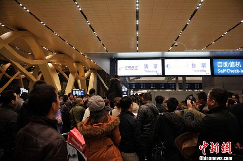 2013年1月5日凌晨,昆明长水国际机场的候机楼内,部分旅客因航班长时间延误情绪激动,围堵航空公司柜台。(摄影:刘冉阳 来源:中新网)