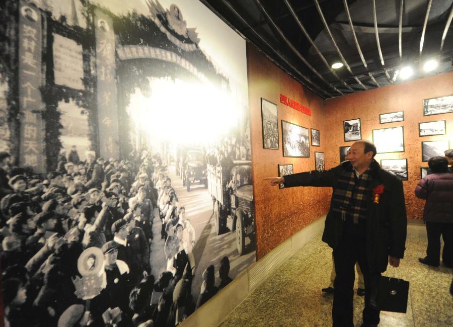 """(3)1月21日,在""""寻根·守望——沐浴圣地洗礼的北京知青""""专题展上,一位北京老知青指出老照片里的自己。"""
