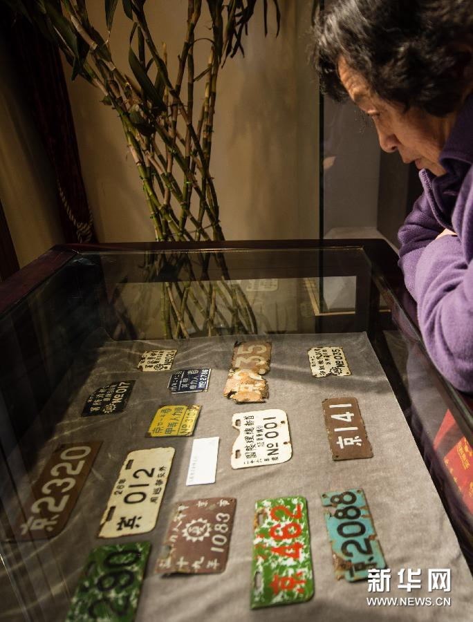 """(5)3月11日,一位南京市民在观看民国时期的""""车牌""""。"""