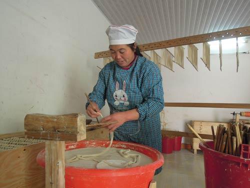 油面合作社的一名妇女正在把油面上筷