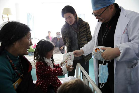 Metog (2nd L) accepts the gifts sent by her doctors when she leaves hospital on May 11, 2014. [Photo/Xinhua]