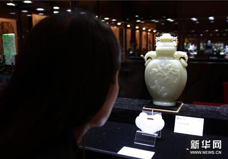 """6月3日,参观者在参观拍品——清代玉器""""白玉花鸟纹盖瓶""""。"""