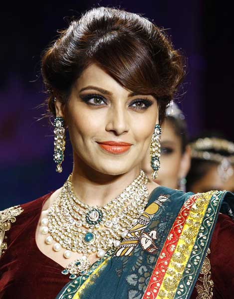 Actress Bipasha Basu strolls the catwalk in a green embroidered skirt and a maroon blouse, showcasing a gorgeous necklace, shoulder dusters, bangles and a cocktail ring.