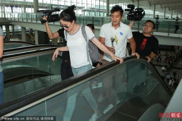 """王菲   7月22日,素颜的王菲今日下午四时身戴上墨镜,穿白色上衣配牛仔裤,现身机场离境大堂。王菲步出离境大堂后,立即转上电梯,记者发现后随即追访,王菲更于电梯上奔跑几步,不时以手掩脸。问到王菲去哪儿?她表示回北京,之后用手推麦克风:""""不要搞到这么大阵仗,你们不要这样啦!""""之后王菲又否认去北京工作。途中有喇嘛呼叫王菲,阿菲亦双手合十回应对方。讲到有指其前夫李亚鹏的绯闻,王菲并无回应。   在办理登机手续时,王菲与助手八卦询问记者在机场等谁,知道记者等张耀扬返港后,即摇头表示不"""