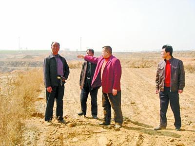 图为王胜(左一)在百果庄园建设现场指导。