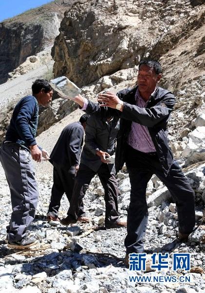 斯那定珠(右一)和工人一起修建香格里拉大峡谷内的公路(2013年9月13日摄)。新华社发