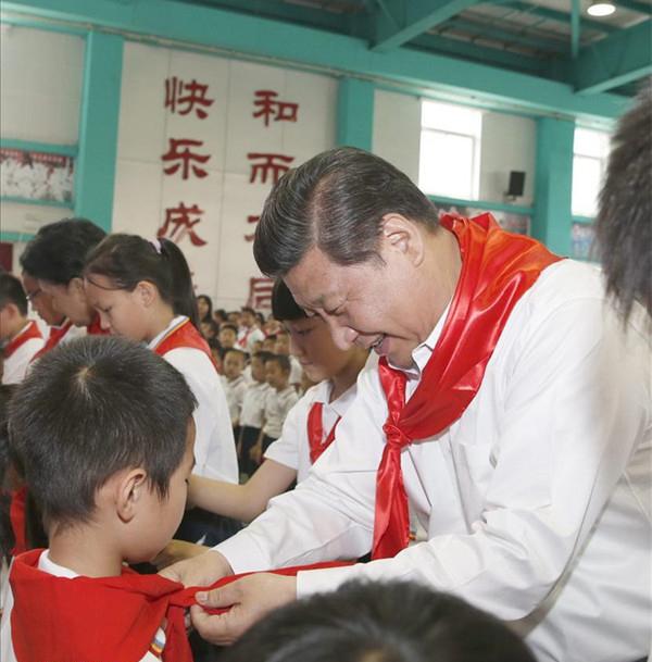 2014年5月30日,在北京市海淀区民族小学的少先队入队仪式上,习近平为新少先队员系上红领巾。