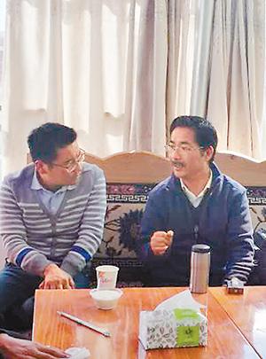 尼玛扎西(右)与基层科技人员交流。