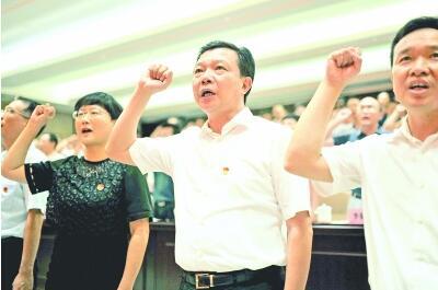 2017年7月1日,杨汉军(中)与机关党员干部一起重温入党誓词