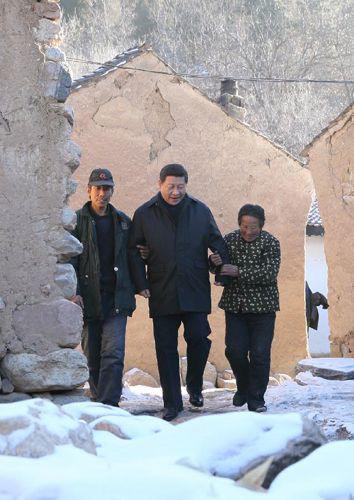 2012年12月30日,习近平来到地处深山的龙泉关镇骆驼湾村,走进困难群众唐宗秀(右)家慰问看望。