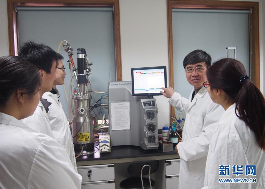王一成(右二)在浙江省农业科学院畜牧兽医研究所向学生讲解干扰素发酵实验(资料照片,2012年5月摄)。