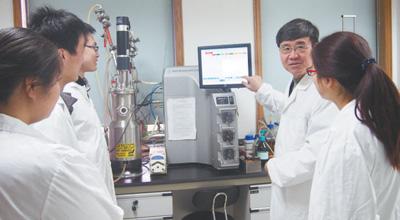 王一成(右二)在浙江省农业科学院畜牧兽医研究所向学生讲解干扰素发酵实验。