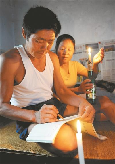 王继才和妻子在烛光下填写巡逻日记。