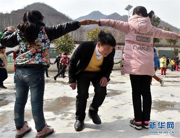 张玉滚在课间与学生们做游戏(3月20日摄)。新华社记者 李嘉南 摄
