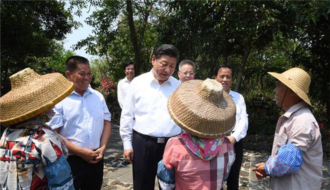 2018年4月13日上午,习近平在海口市秀英区石山镇施茶村考察时,同村民亲切交谈。