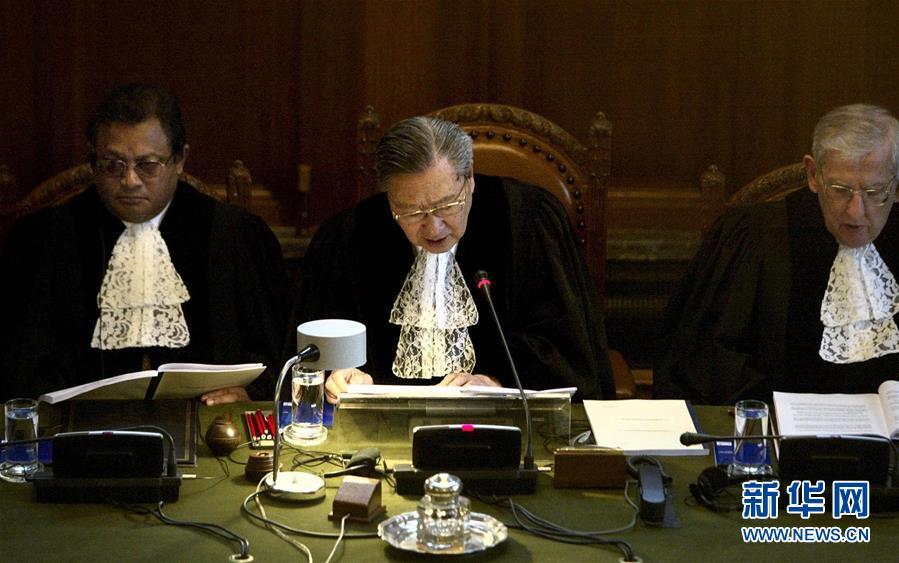 2004年7月9日,国际法院院长史久镛大法官(中)在荷兰海牙宣读法院裁定书。