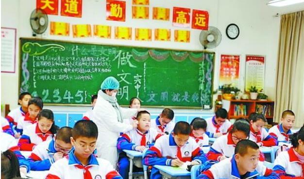 卫生监督人员对学生进行传染病防控筛查。