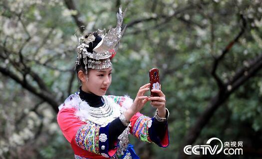 一名苗族姑娘用手机在广西柳州市融安县东起乡铜板屯拍摄美景。(谭凯兴 摄)