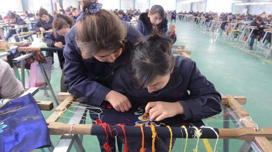 3月29日,工人们在喀什丝路行科技研发有限公司刺绣产业扶贫车间中上班。