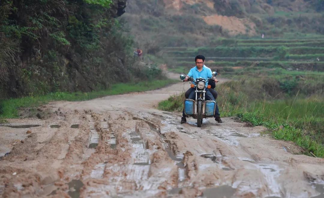 ↑在融水苗族自治县杆洞乡杆洞村,扶贫工作队员黄振霜骑摩托车进村(4月27日摄)。