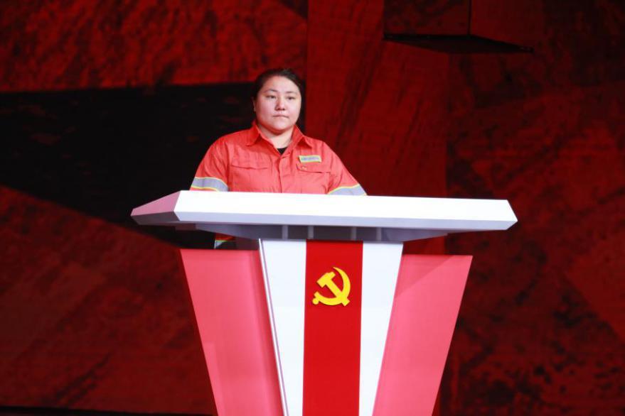 图为彩排现场,身着工作服的李萌站在初心台上