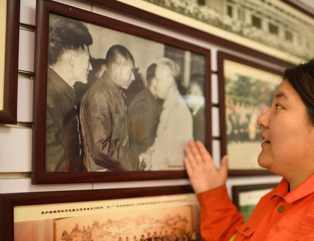 圖為李萌站在《劉少奇接見時傳祥》的歷史照片前
