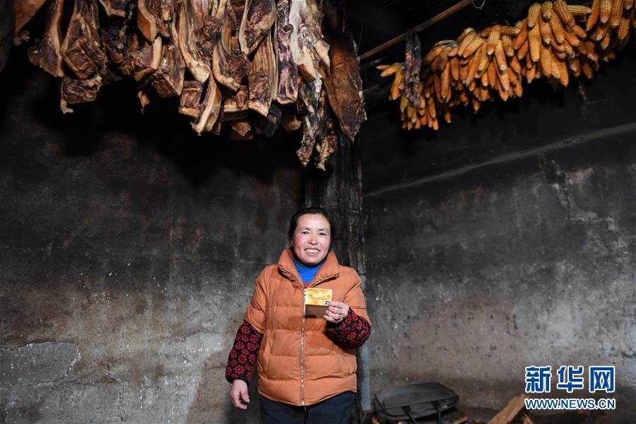 湖南龙山县翻身村村民李红云在展示自家的储蓄卡(3月10日摄)。新华社记者 薛宇舸 摄