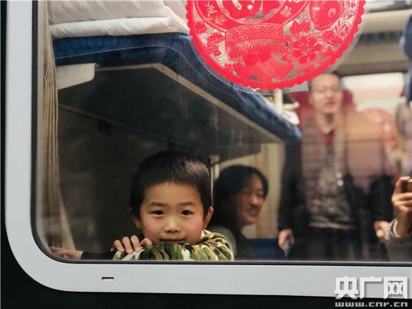 1月10日,在春运首趟增开的北京—南通K4051次列车上,一位小乘客透过车窗向外张望(央广网记者 王晶 摄)