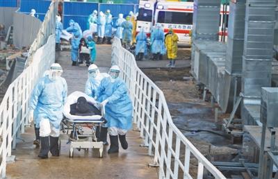 近日,医护人员将患者转运至武汉火神山医院病房。新华社记者 肖艺九摄