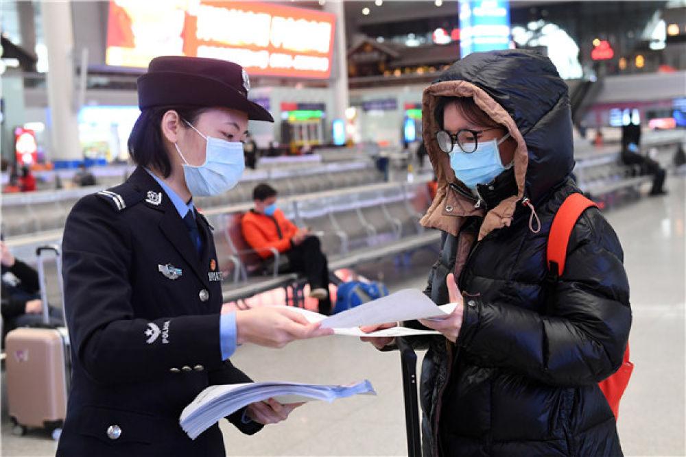 在广西南宁东站,南宁铁路公安处女民警花子惠(左)将自己创作的疫情防控宣传漫画送给乘客(2月4日摄)。新华社记者 陆波岸 摄