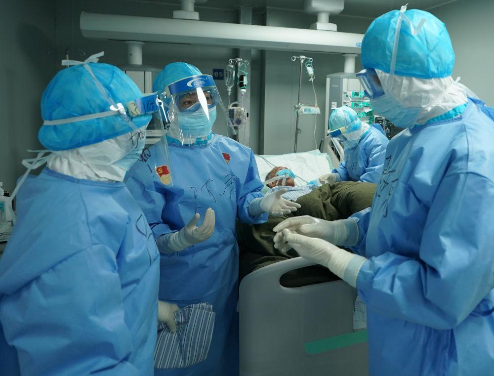在武汉火神山医院,重症医学一科护士长陈静(中)与医生讨论患者病情(3月17日摄)。新华社记者 王毓国 摄