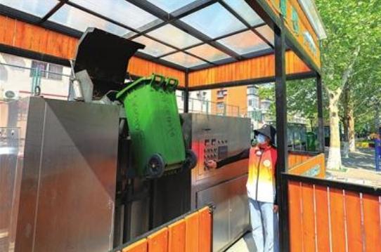 """志愿者按键操作,将厨余垃圾倒入""""厨余垃圾资源化一体机"""",经过搅拌、发酵,24小时后变""""废""""为""""肥""""。"""