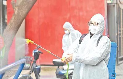 武汉市洪山区珞南街广八路社区书记对健身器械进行消毒。