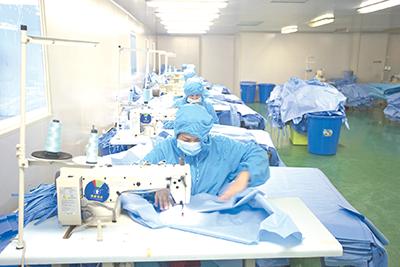 广西柳州圣美康医疗器械有限公司职工加班加点,赶制疫情一线医用手术衣。(图片由广西柳州市委组织部提供)
