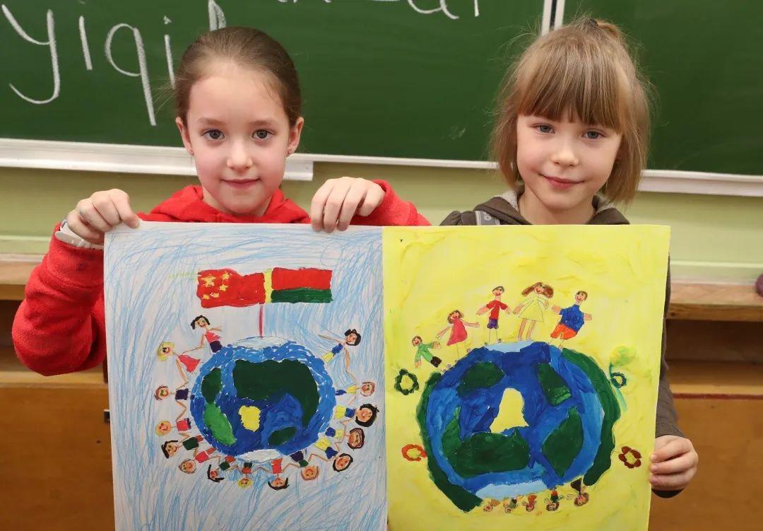 2月27日,在白俄罗斯首都明斯克,两名小学生展示自己支持中国抗击新冠肺炎疫情的绘画作品。新华社发(任科夫 摄)