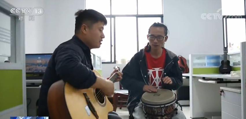 学校老师顾亚和胡静在办公室用吉他和鼓合奏