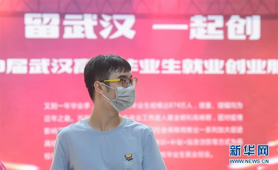 一名求职者在江汉大学校园内举办的招聘会现场寻找合适的岗位(6月1日摄)。这是疫情发生后,武汉举办的首场高校毕业生专场线下招聘会。