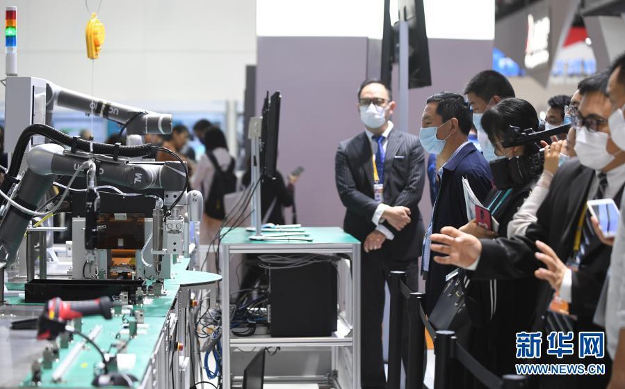 2020年11月6日,在进博会技术装备展区,人们在西门子展台观看人机协作的智能化单元生产线。新华社记者 李任滋 摄