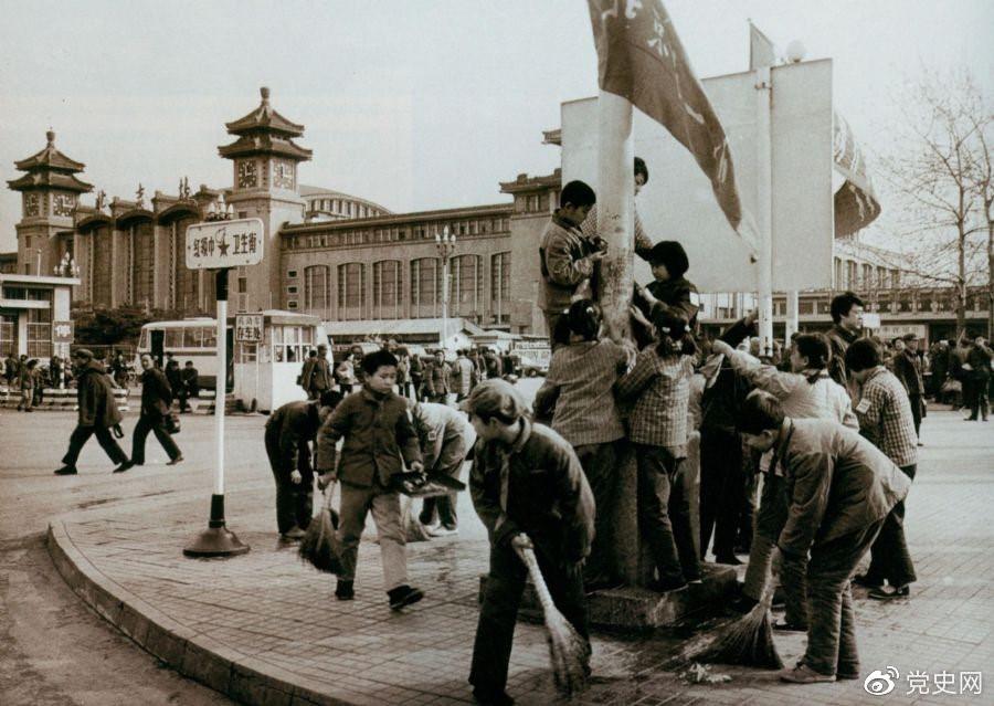 """1981年2月25日,全国总工会等九个单位发出倡议,开展""""五讲四美""""文明礼貌活动。图为北京铁路一小的少先队员在北京站西街打扫卫生。"""