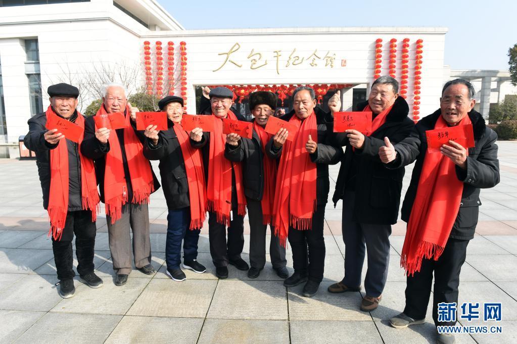 """2月3日,在安徽省滁州市鳳陽縣小崗村,8位""""大包干""""帶頭人在大包干紀念館前展示自家領取的集體經濟收益股權分紅。新華社記者 周牧 攝"""
