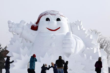 Tourists pose near a snow sculpture during the 26th Harbin International Ice and Snow Festival at a park in Harbin, Heilongjiang province, January 5, 2010.[Photo/Agencies]