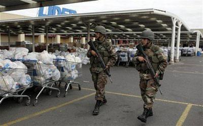 Soldiers walks past bags containing aid to be distribute among earthquake victims at a supermarket in Concepcion , Chile, Wednesday, March 3, 2010. (AP Photo/Natacha Pisarenko)