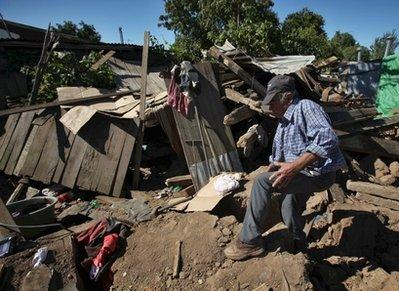 Earthquake victim Jose Cerda, 83, enters in his destroyed house in Parral, Chile, Monday, March 15, 2010. An 8.8-magnitude earthquake hit central Chile last Feb. 27, causing widespread damage. (AP Photo/Martin Mejia)