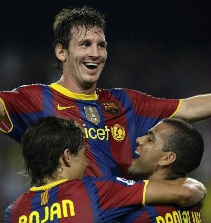 Barcelona's Lionel Messi (top) celebrates his goal with Bojan Krkic (L) and Dani Alves during their Spanish Super Cup second leg soccer match against Sevilla in Barcelona August 21, 2010.(Xinhua/Reuters Photo)