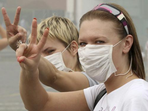 Women, wearing masks to protect themselves from the smell of heavy smog caused by peat fires in nearby forests, gesture as they walk along Red Square in central Moscow August 7, 2010. Dense clouds of acrid smoke from peat and forest fires choked Russia's capital on Friday, seeping into homes and offices, diverting planes and prompting exhausted Muscovites to wear surgical masks to filter the foul air.(Xinhua/Reuters Photo)