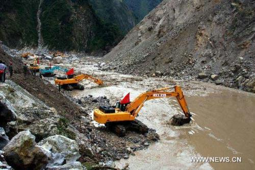 Cranes remove barriers to speed up flood discharge in landslide-hit Mianzhu City, southwest China's Sichuan Province, Aug. 21, 2010. Rescuers have resumed the road and waterway on Saturday to send the relief supplies to isolated local residents stranded in the mountains after heavy rain triggered mudslides in Mianzhu on Aug. 13. (Xinhua)