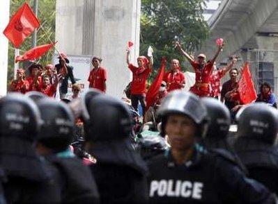 "Anti-government""redshirt""protesterswavesredflagsastheystandontopofabarricadebuiltwithbamboopolesandtyresfacingriotpoliceatanintersectionclosetotheSilomRoadfinancialdistrictinBangkokApril21,2010.Thaianti-governmentprotestersfortifiedtheirmainrallysiteinanupmarketshoppingareaofBangkokafterthegovernmentwarnedtheywouldbeevicted,settingupapotentiallybloodyclashinthecapital.REUTERS/EricGaillard"