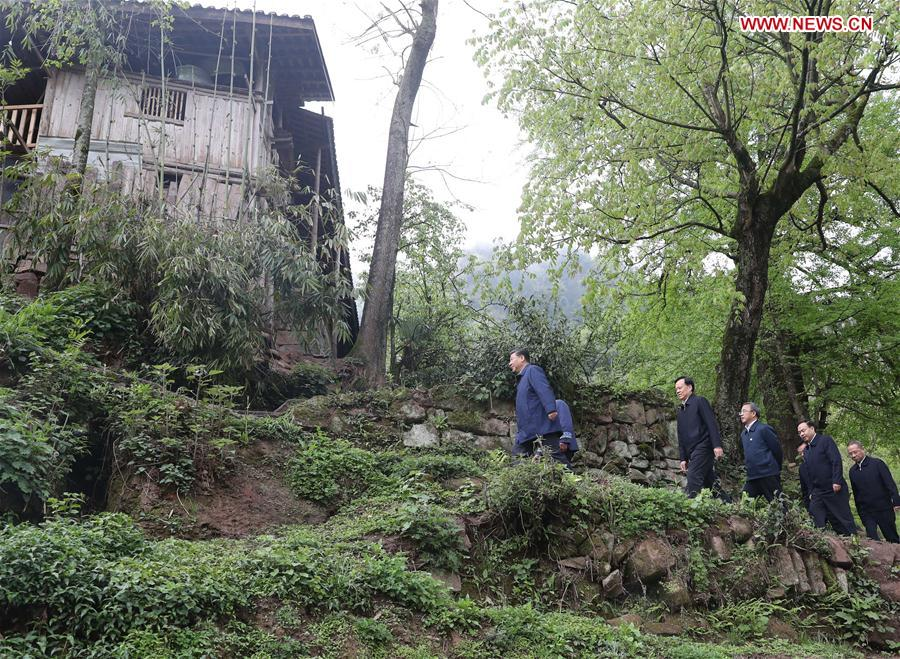 Chinese President Xi Jinping, also general secretary of the Communist Party of China Central Committee and chairman of the Central Military Commission, walks to a villager