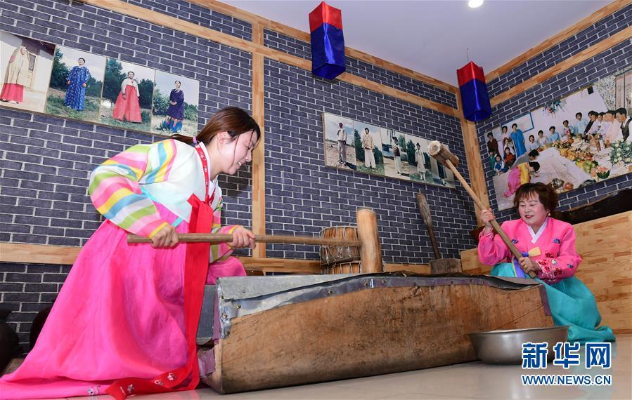在红旗村民俗体验馆中,游客学做打糕(4月16日摄)。新华社记者 林宏 摄