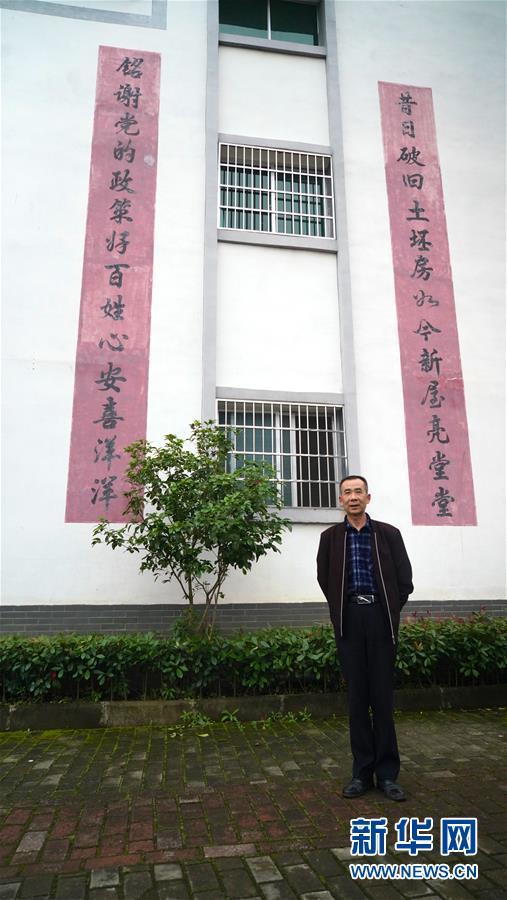5月7日,江西瑞金华屋村居民华辉平在自家房前留影。 新华社记者 胡晨欢 摄